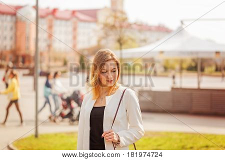 Portrait of cute girl smiling to camera in city on bulding background in sunny day.