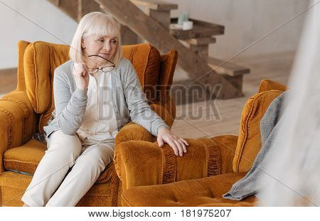 Now I am alone. Unhappy pessimistic aged woman sitting In the armchair and holding her glasses while looking at the empty armchair near her