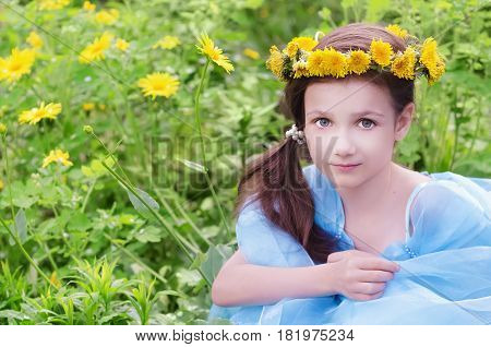 Little girl in wreath of dandelions sitting in the flower meadow. Selective focus