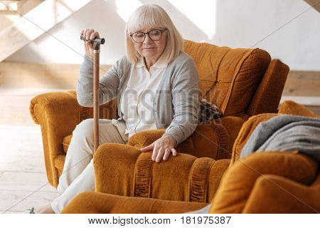 I cant live without him. Depressed aged unhappy woman sitting in the armchair and grieving about her husband while feeling lonely