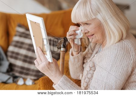 Do not cry. Sad miserable unhappy woman holding a paper tissue and wiping away her tears while looking at the photograph