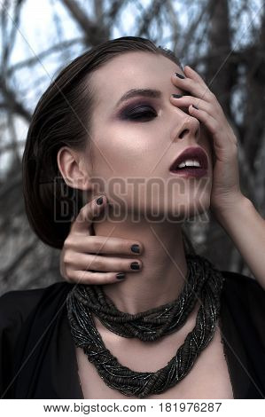 Pretty Brunette Girl With Bright Makeup And Purple Lips Wearing Black Posing Outdoors On Blue Summer