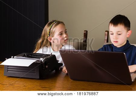 Girl angry because she has to work on an old typewriter while her brother is working on a modern laptop