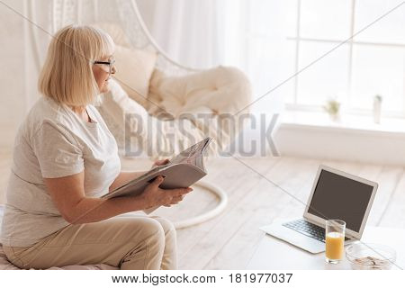 Pleasant entertainment. Positive joyful senior woman holding a magazine and turning over its pages while resting at home