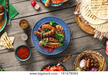 Dinner party food concept. Dinner table with grilled sausage tortilla wraps and different dishes on wooden table rustic style
