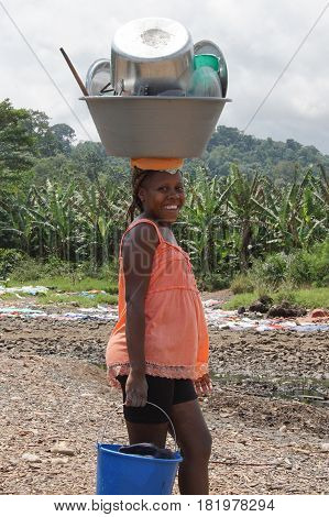 RIBEIRA AFONSO, SAO TOME - JANUARY 29, 2017: Young girl carrying ready dishes on her head, Fishermen village Ribeira Afonso, Sao Tome Island on January 29, 2017 in Sao Tome and Principe, Africa