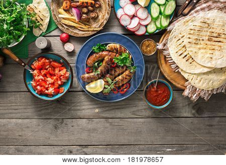 Dinner table with grilled sausage tortilla wraps and different dishes on wooden table with border rustic style. Dinner party food concept