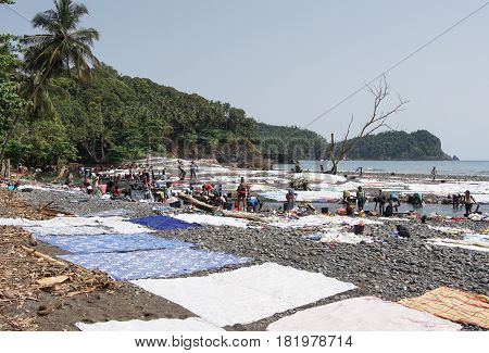 PRAIA MESSIA ALVES, SAO TOME - JANUARY 29, 2017: Women washing clothes on Praia Messia Alves on January 29, 2017 in Sao Tome, Africa
