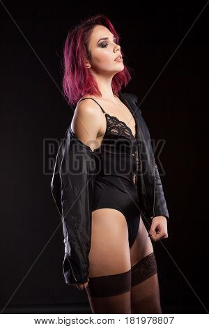 Sensual redhead woman in lingerie and leather jacket in studio photo on black background. Erotica and sensuality. Passion and fashion
