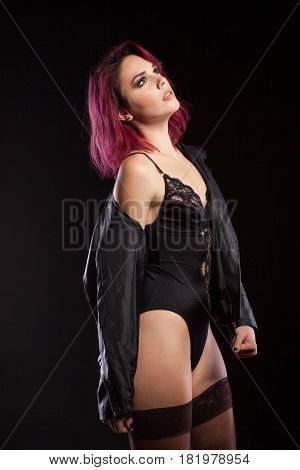 Sensual redhead model in lingerie and leather jacket in studio photo on black background. Erotica and sensuality. Passion and fashion