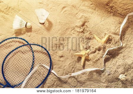 Badminton rackets net shuttlecock and starfish on the sand top view. Summer background
