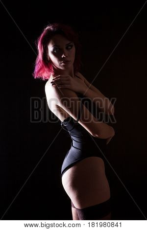 Gorgeous redhead in lingerie and leather jacket in studio photo on black background. Erotica and sensuality. Passion and fashion