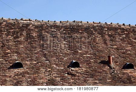 Terracotta roof tiles on ancient building in rural France