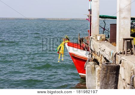 Red fishing boat stay harbor without fisherman in ASEAN style. Sea and blue sky are background. poster