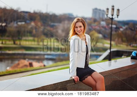 Portrait of young beautiful woman smiling to camera in city on bulding background in sunny spring day