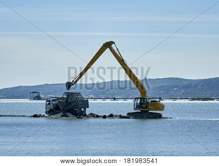 Excavator loading sand and cobblestone into a lorry on a lake
