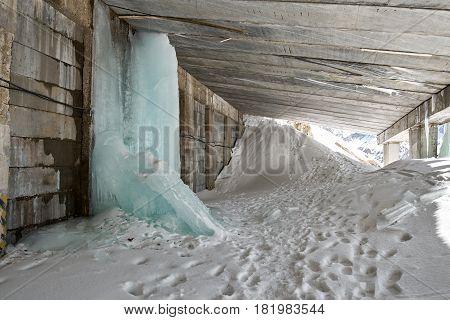 Mountain road in snow drift through a passage