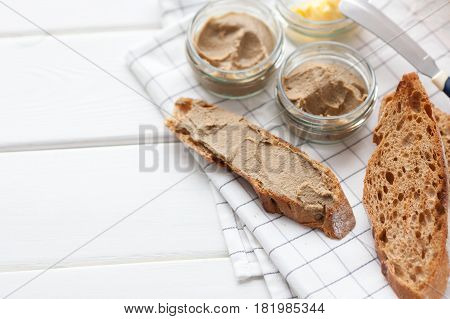 Bread with veal and rabbit pate with butter on a textile background. Top view with copy space.