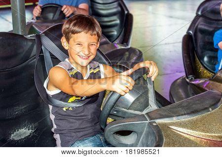 Smiling boy in electric bumper car amusement park.