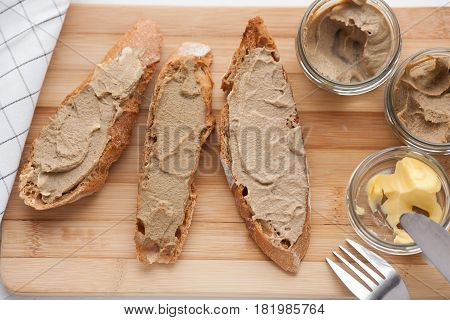 Bread with veal and rabbit pate with butter on a bamboo board. Top view.