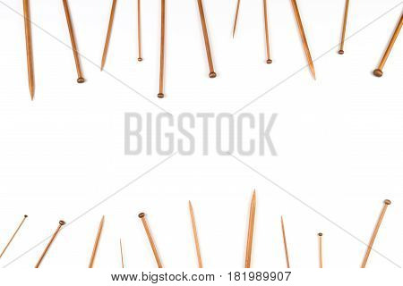 Wooden bamboo knitting needles arranged as frame border on white background. Top view. Copy space for text
