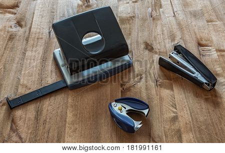On the wooden surface are a stapler anti-stapler and puncher