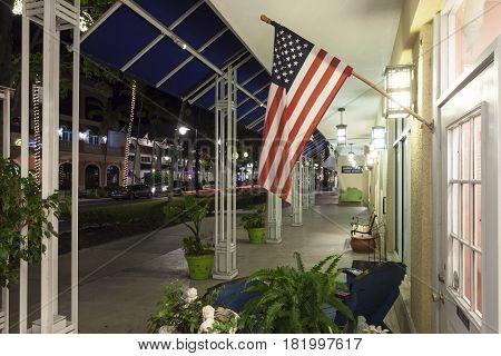 Naples Fl USA - March 21 2017: National flag of the united states at the display window of a shop in Naples downtown district. Florida United States