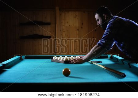 hansome man playing billiards alone in a big room