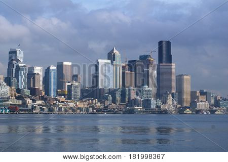 SEATTLE, WASHINGTON, USA - JAN 25th, 2017: A view on Seattle downtown from the waters of Puget Sound. Piers, skyscrapers and Ferris wheel in Seattle city before sunset.
