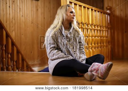 girl sitting on the floor near the wooden staircase railing