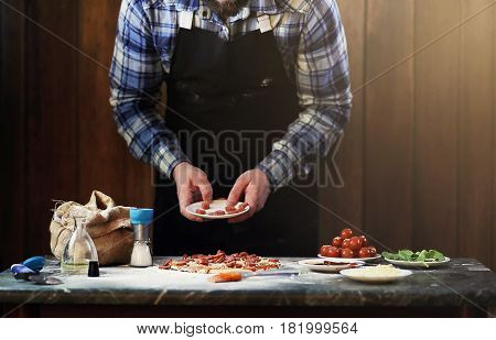 a man preparing a pizza, knead the dough and puts ingredients