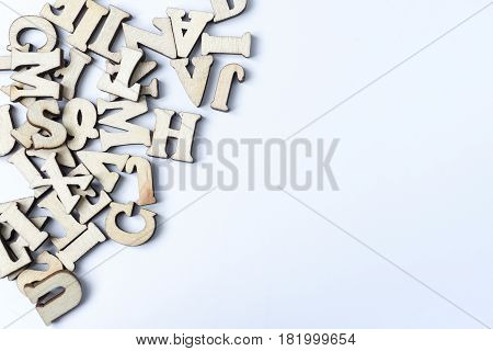Many different wooden letters on a white background.