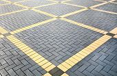 Texture of gray and yellow patterned paving tiles on the ground of street perspective view. Cement brick squared stone floor background. Concrete paving slab flagstone. Sidewalk pavement pattern. poster