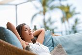 Home lifestyle woman relaxing sleeping on sofa on outdoor patio living room. Happy lady lying down on comfortable pillows taking a nap for wellness and health. Tropical vacation. poster