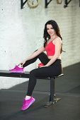Young beautiful girl in sports attire resting between training sessions poster
