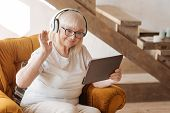 Favourite entertainment. Positive delighted elderly woman wearing headphones and holding a tablet while listening to music poster