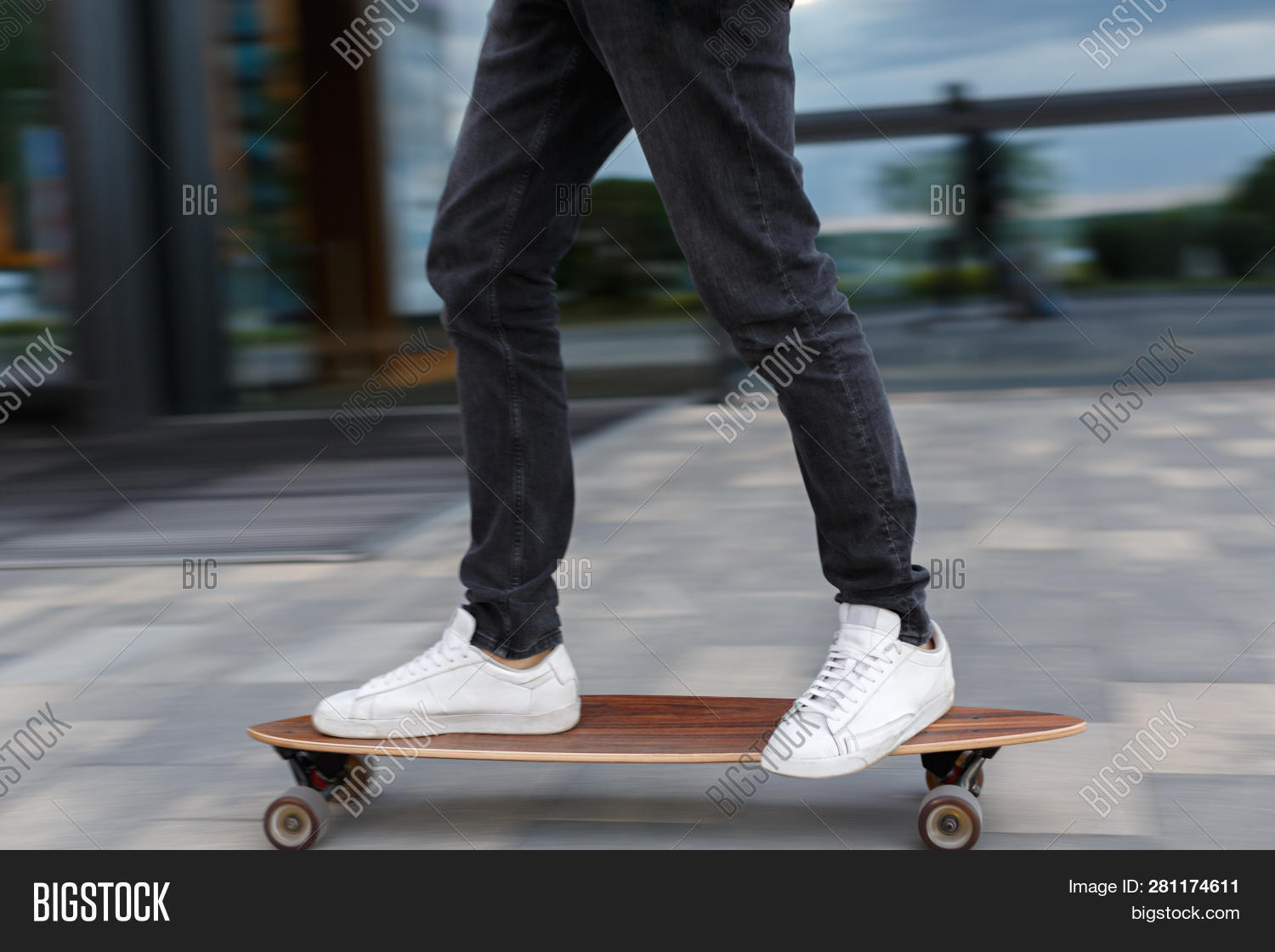 Cropped shot of young man in black jeans and white sneakers riding on longboard to the left in urban area hurry on a date photo in motion side view