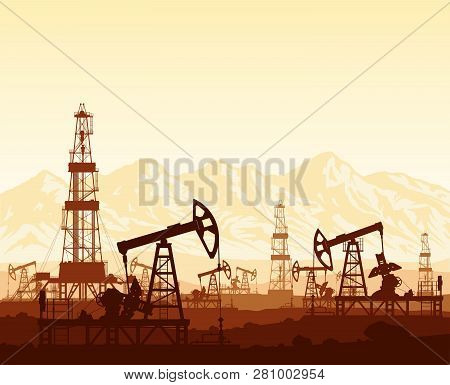 Oil Pumps And Drilling Rigs Silhouettes At Large Oilfield On Huge Mountain Range Background At Sunse