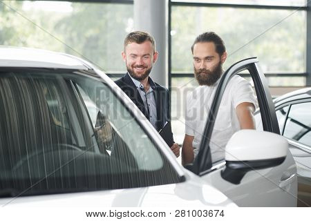 Car Dealer Showing Car To Customer. Brutal Bearded Man In White Shirt Looking At Car, Observing. Men
