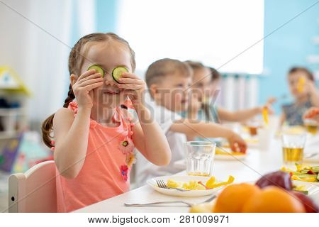 Funny Kid Eating Healthy Food In Kindergarten Or Daycare