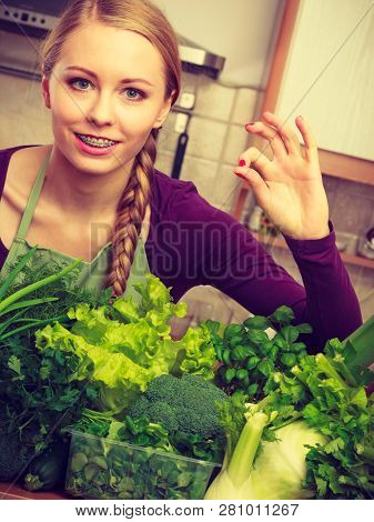 Woman In Kitchen With Many Green Leafy Vegetables Making Thumb Up Hand Sign Gesture. Young Housewife