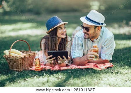 Couple Lying On A Picnic Blanket In A Park With A Picnic Basket Filled With Fruit, They Are Using Di