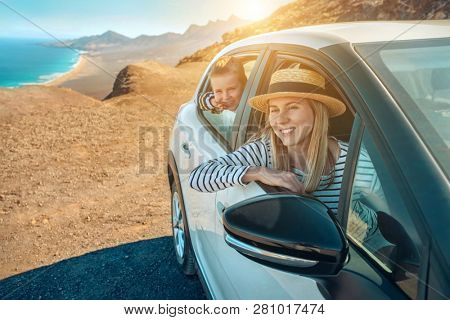 Happiness young woman in hat and her son sitting in white car and looking on beautiful ocean coastline view. Freedom, Travell, Family, Journej, Trip, Shooting concept.