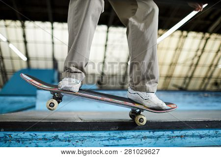 Contemporary skateboarder riding on edge of parkour facilities while training at stadium poster