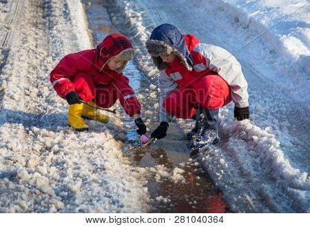 Two Boys In Rainboots Launching The Paper Boat At The Creek With Melting Snow On Sunny Spring Day, O