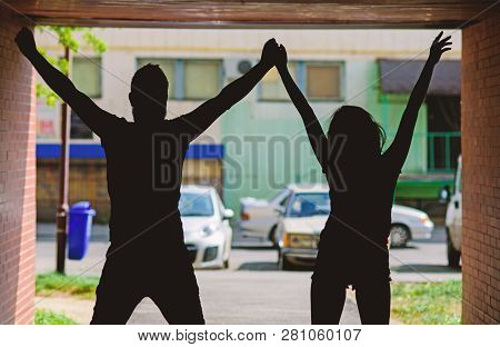 Silhouette Couple In Love Against Urban Background. Couple Meet In Porch Or Entrance Hall. Youth On