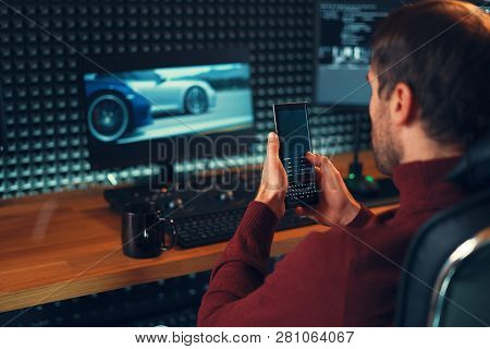 Man freelancer holding mobile phone working on footage, video, design. Cars on monitors in the background. poster