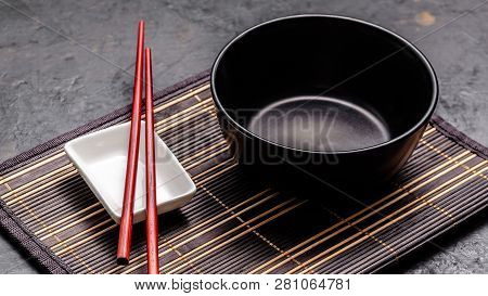 Empty Japanese Dishes. A Black Ceramic Bowl For Chinese Noodles Or Thai Soup Lies On A Bamkuk Rug. W