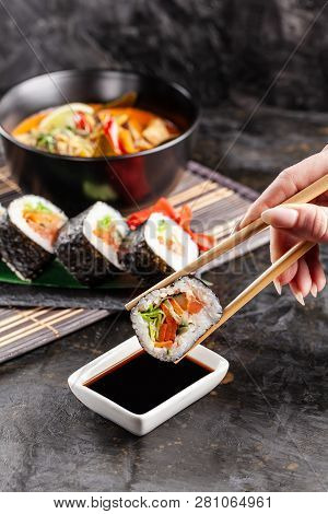 Concept Of Asian Cuisine. The Girl Is In A Chinese Or Japanese Restaurant Sushi, Holds Wooden Sticks