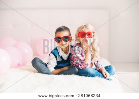 Portrait Of Two Happy White Caucasian Cute Adorable Funny Children Wearing Heart Shape Glasses. Boy
